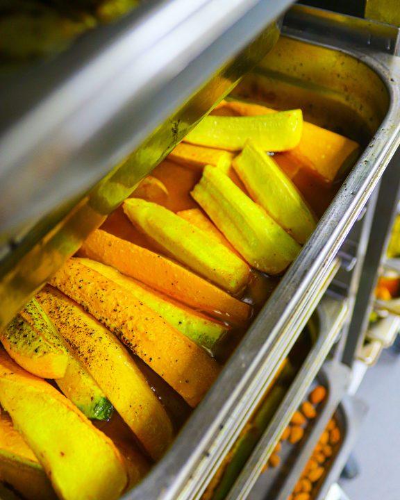 Lækre, stegte gule squash på et stålfad - tilberedt i Glad Service