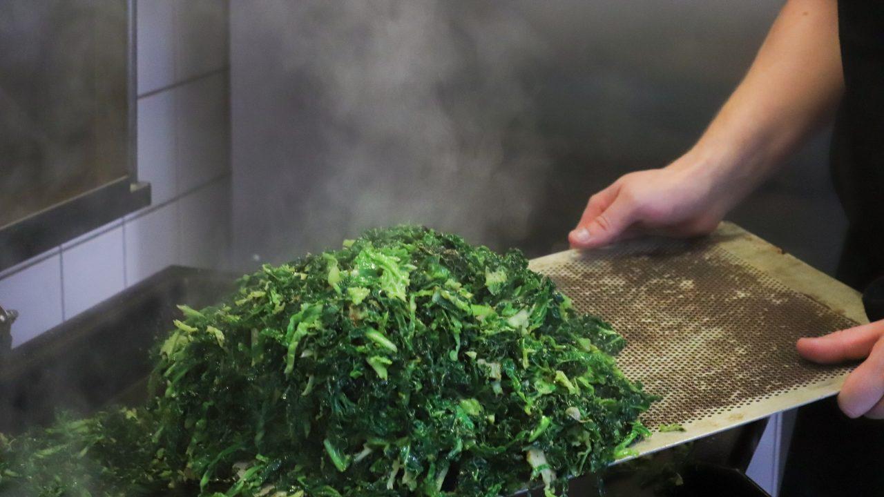 Sprød, dampende grønkål holdes frem af en medarbejder i Glad Mad.