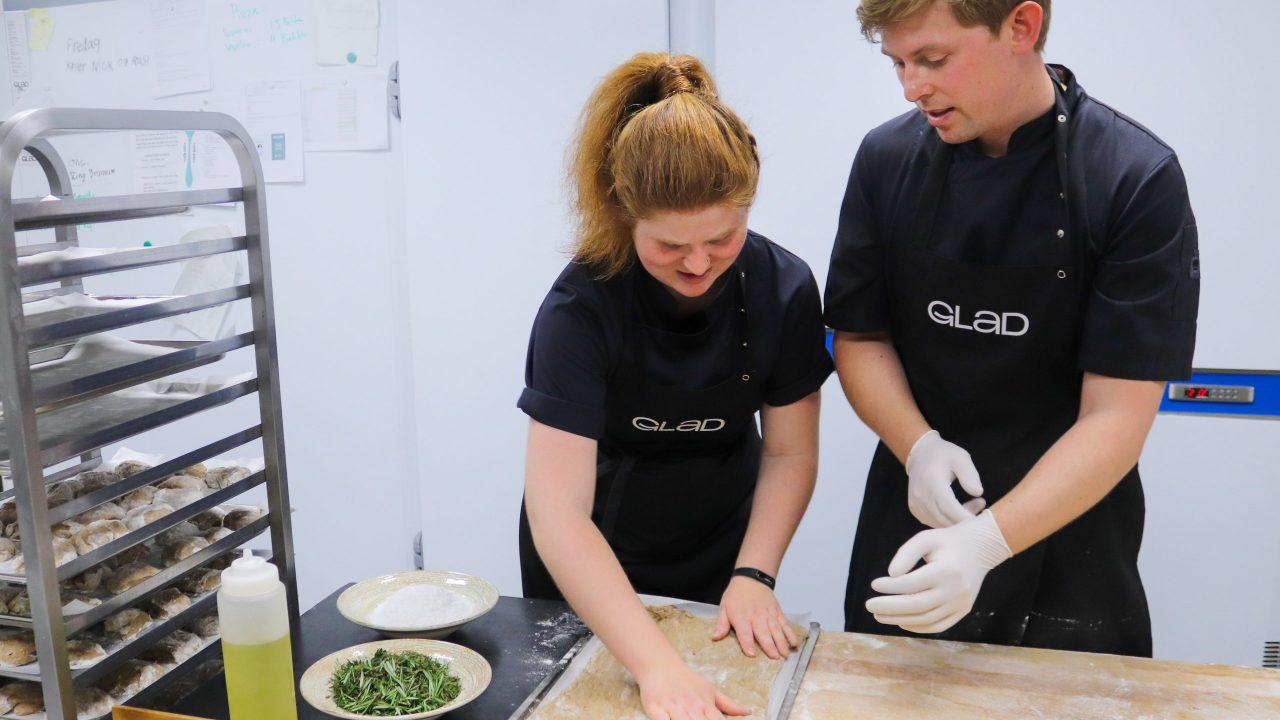 En medarbejder på særlige vilkår og en ordinær medarbejder i Glad Mad hjælpes om at drysse olie, havsalt og friske krydderurter over hjemmebagt focacciabrød, inden det skal i ovnen.
